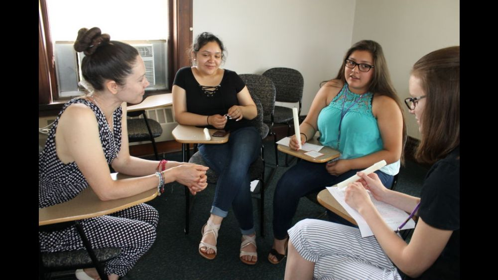 4 Encuentro participants seated in a circle, working on a project together