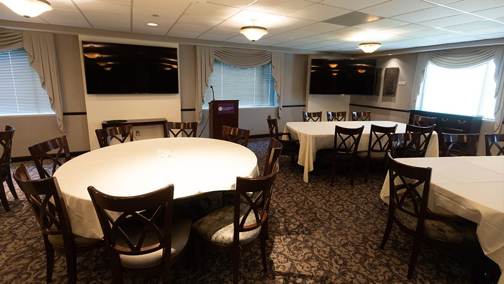President's Dining Room from center, view of tables, tv screens and podium