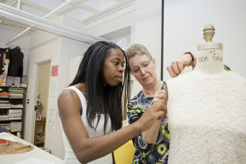 a faculty member helps a student work on a garment hung on a dressmaker's dummy