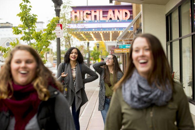 Students walk down Cleveland Ave by the Highland movie theater