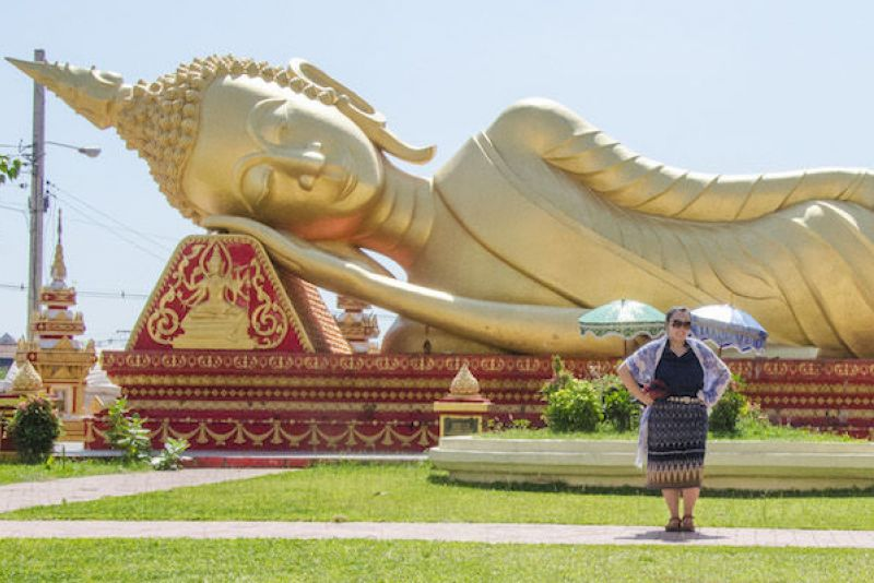 Fulbright Grant scholar posing in front of giant gold statue in Laos