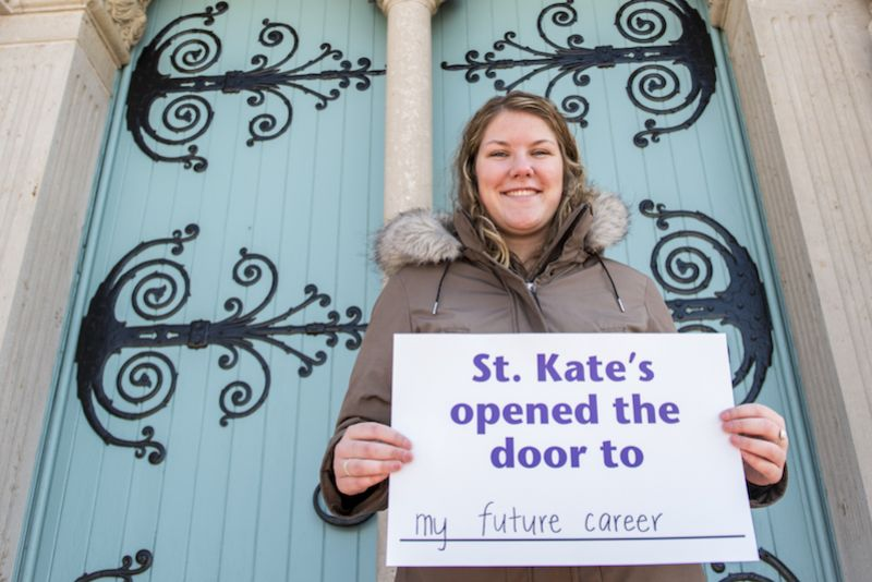 St. Kate's alumna in front of the Chapel doors, holding a sign saying St. Kate's opened the door to my future career