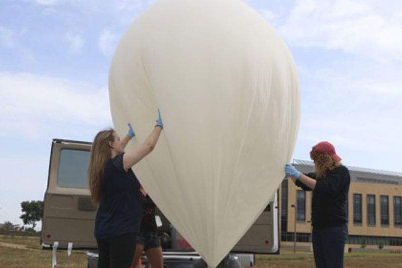 Professor Erick Agrimson inflating a weather balloon, while his students hold it steady. Photo by Ashley de los Reyes '15