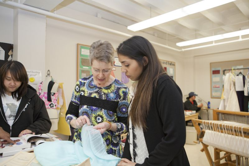 Faculty member works with a student in a fashion merchandising and apparel design classroom