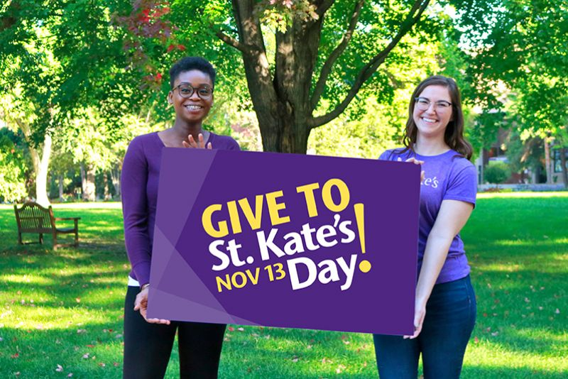 Mary and Allyssa, the Give to St. Kate's Day spokeswomen, holding a sign that says Give to St. Kate's Day November 13.