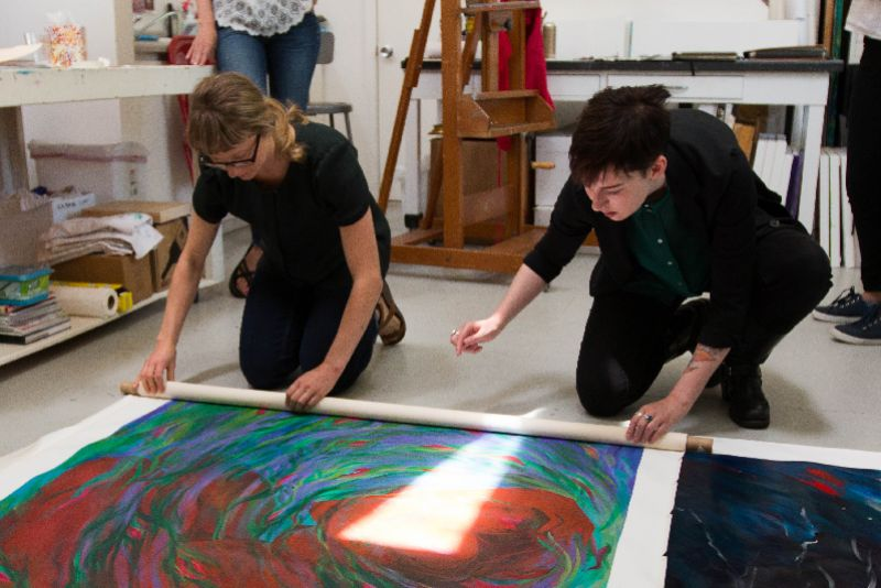 Two women work on large paintings at the Women's Art Institute