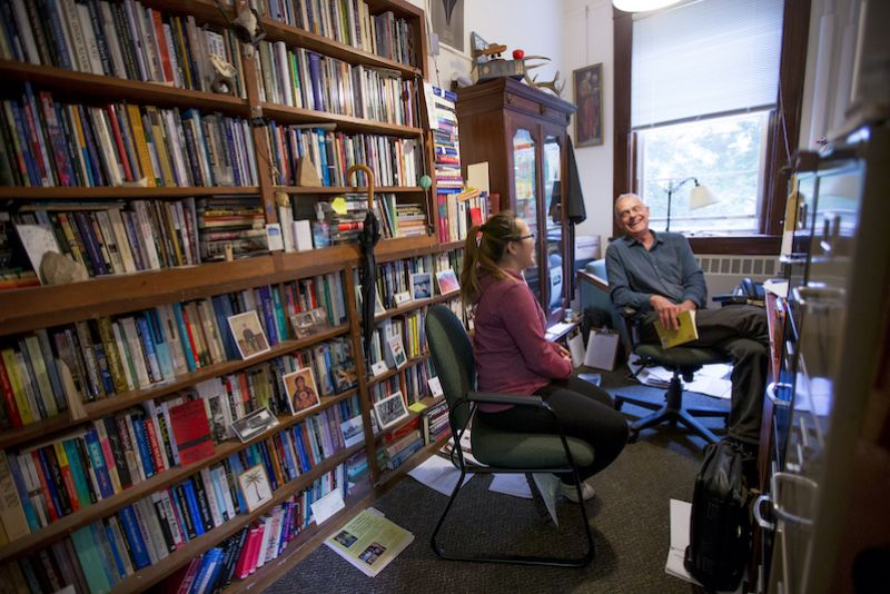 Professor Robert Grunst and a student in an office full of books