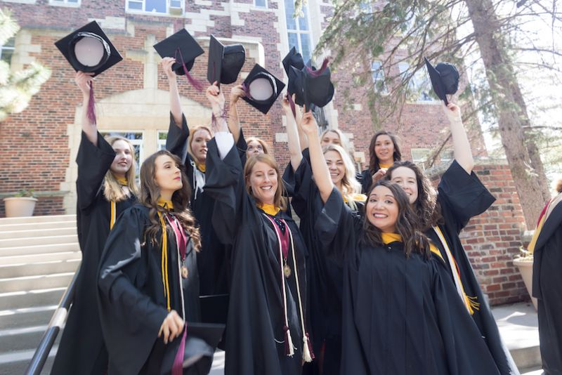 A group of graduates toss their caps on the Fontbonne steps