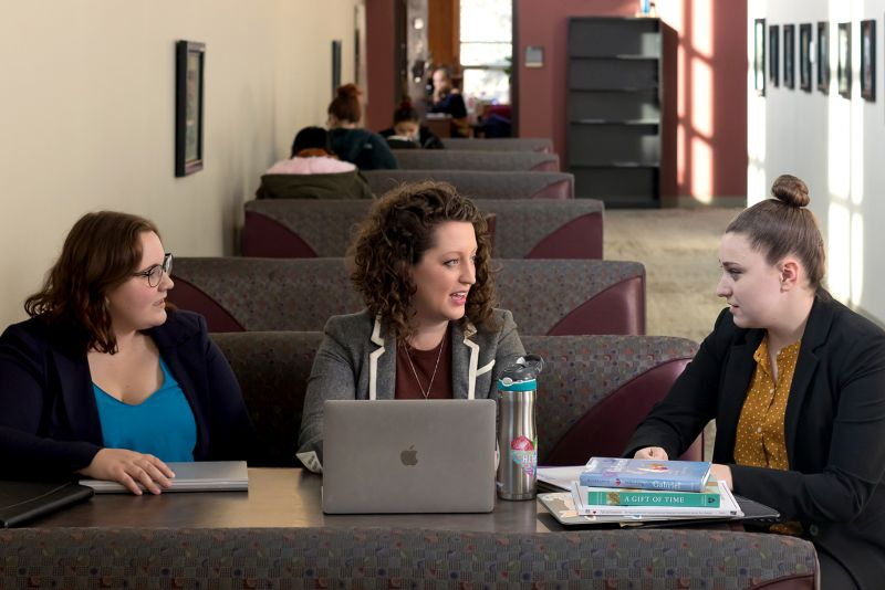Professor Katie Campbell works with two students on a collaborative research project.