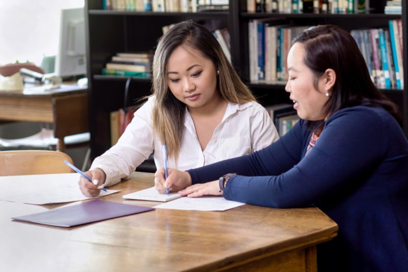Mysee Chang helps a St. Kate's student with a fellowship application