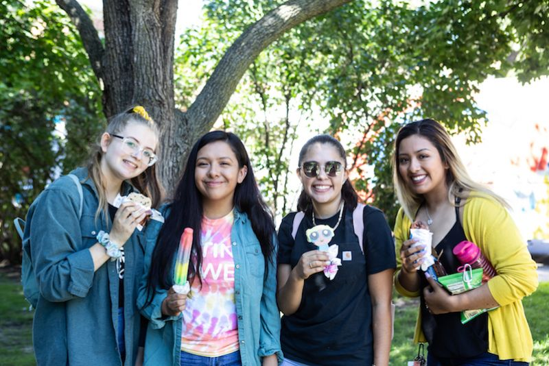 Four St. Kate's students smile with ice cream treats at the 2019 opening celebration picnic.