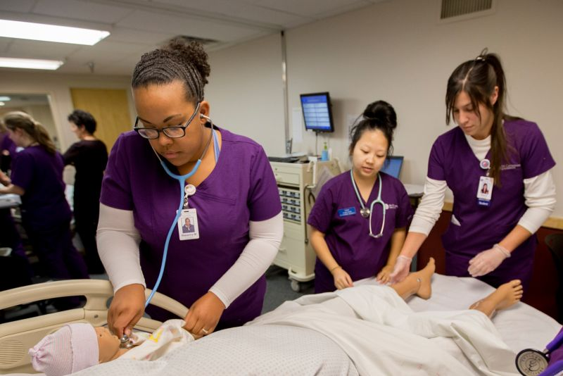 In a simulated clinical setting, one nursing student performs an assessment with a stethoscope as two additional students observe and collaborate. All wearing purple scrubs.