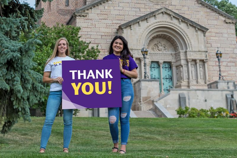 Two St. Kate's alumnae hold a sign that says Thank You