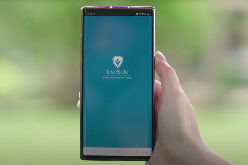 Picture of the St. Catherine University LifeSafe App on a smartphone, held by a hand on a blurred green background. Students, faculty, and staff submitted recommended changes to protect the community from intimate partner violence.