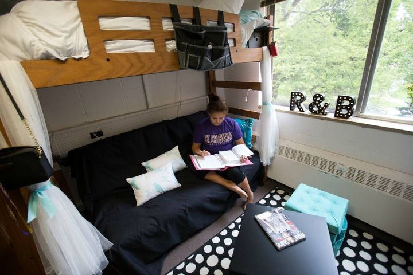 student on bunk bed in St. Mary Hall dorm room
