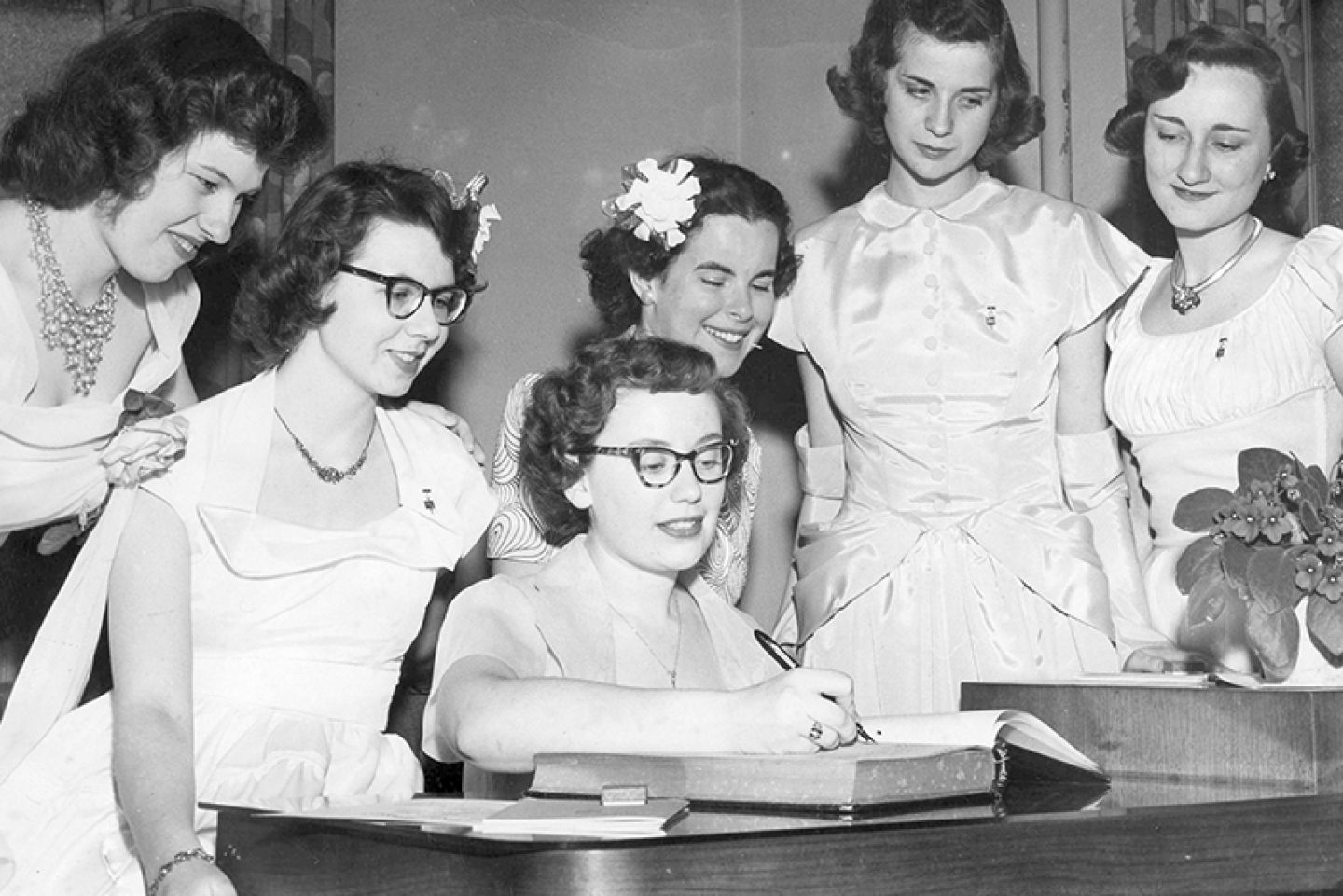 Historical image of St. Kate's students signing the Phi Beta Kappa book as new inductees