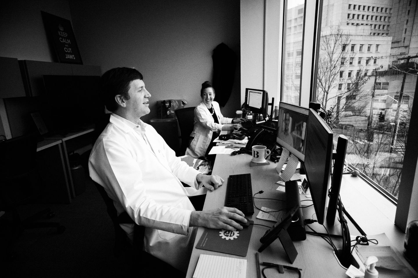Black and white photograph of St. Catherine University alumna Andrea Burgess MPAS'15, PA-C, (right) and Dr. Sam Bobek, DMD, MD, FACS, in the Seattle Jaw Surgery clinic in Seattle, Washington. They are both smiling, seated in front of computers, facing a window. Photo Credit: Panravee Photography
