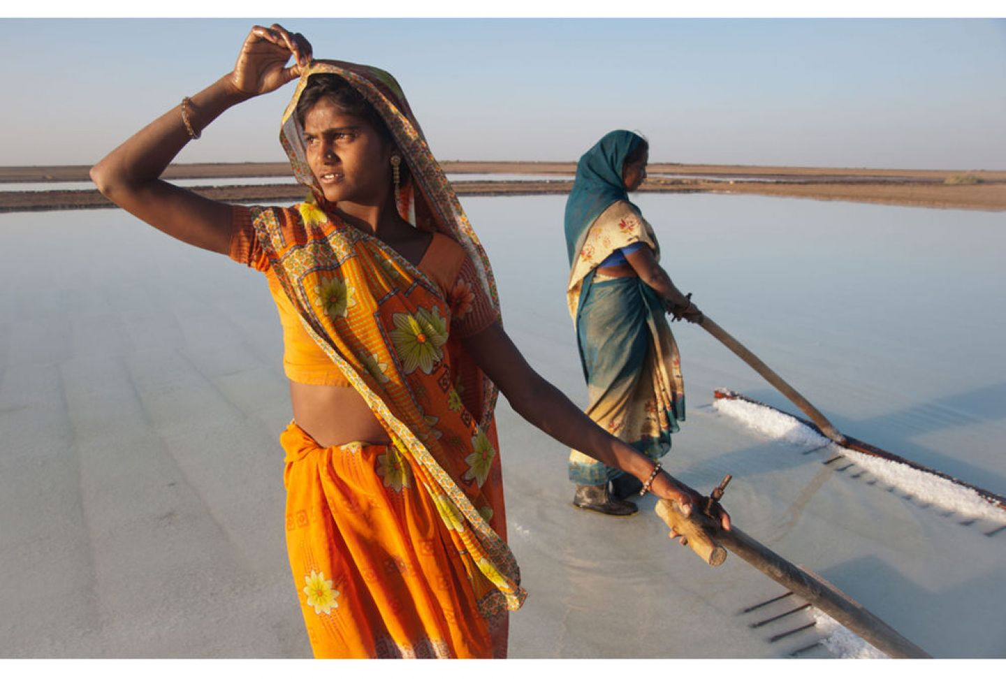 "Photo title is ""Ripple Effect Image"" - shows two (possibly Indian) women in saris standing on sand in ankle-deep water, and using tools that look like large rakes"