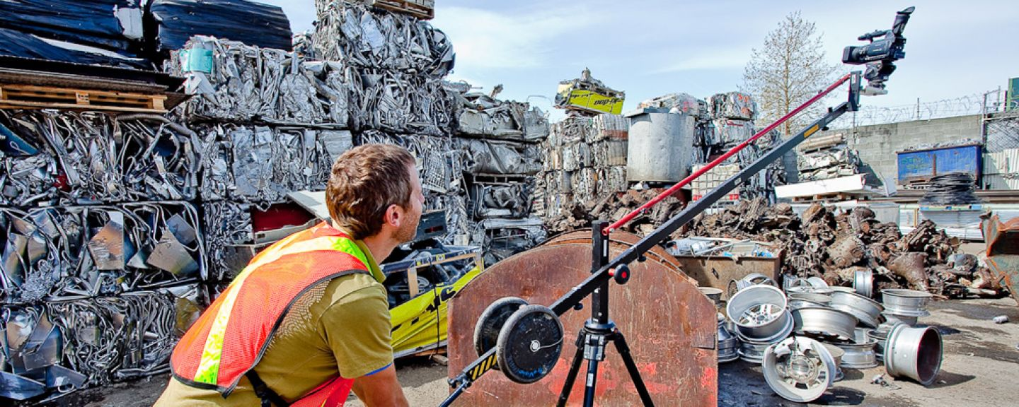 Photo of a man operating a movie camera in an industrial area with stacked bales of crushed metal (auto parts being prepared for recycling?)