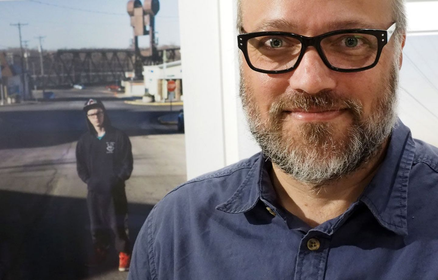 Photographer and Associate Professor Todd Deutsch with one of his photographs from a 2016 exhibit at the Catherine G. Murphy Gallery. Photo by Brad Stauffer